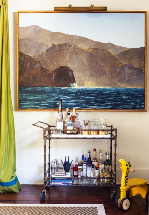 A fully stocked bar cart (who doesn't love a portable party?) and a painting by Garrett Speirs create a moment on an otherwise empty wall.
