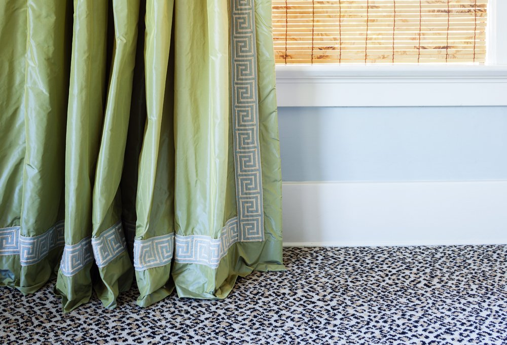 The green taffeta curtains with Greek key trim display the 1-inch break that Yager swears by. Their juxtaposition against the leopard carpet is one of her favorite moments in the house.