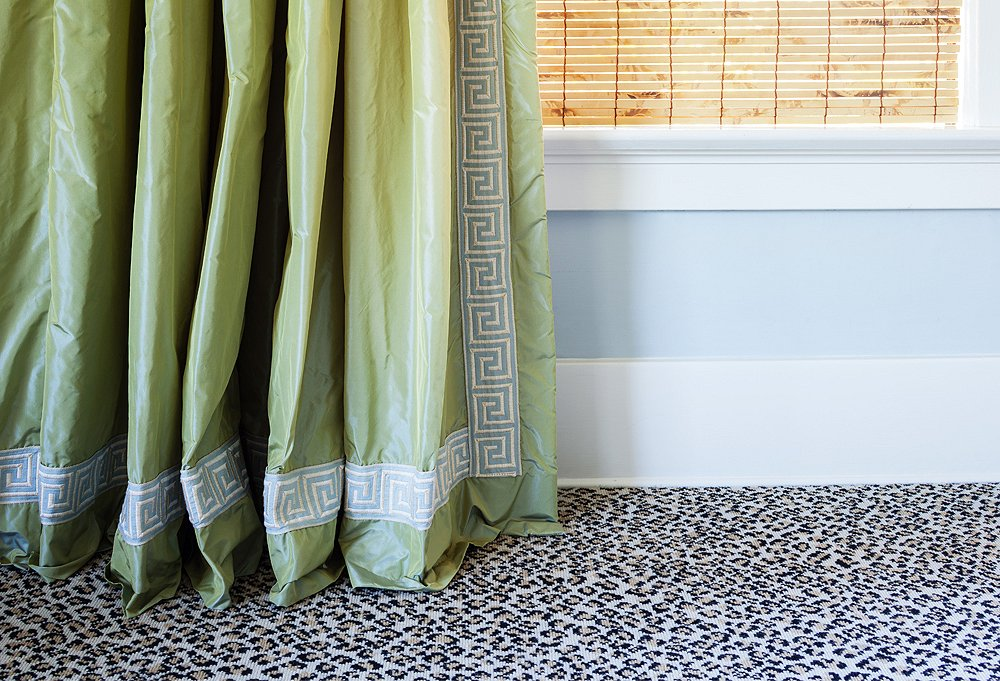 The green taffeta curtains with Greek key trimdisplay the 1-inch break that Yager swears by. Their juxtaposition against the leopard carpet is one of her favorite moments in the house.