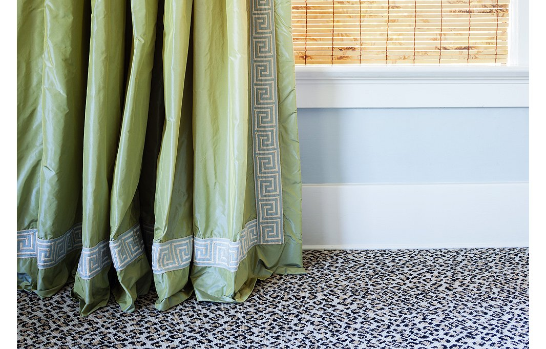 The green taffeta curtains with Greek key trim display the one-inch break that Megan swears by. Their juxtaposition against the leopard carpet is one of her favorite moments in the house.