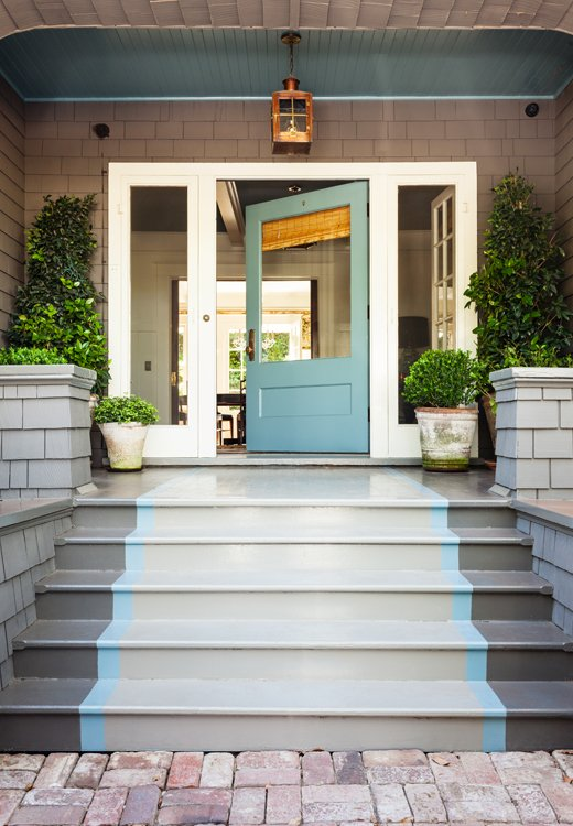The door color, Benjamin Moore's Stratton Blue, is continued into the foyer. A light from Bevolo casts a warm glow on the porch when night falls.