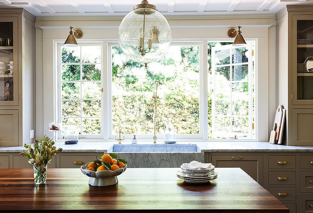 Though the kitchen is new, Yager referenced the original woodwork on the ceilings and brought in traditional touches, from the old-fashioned cabinetry to the island built to look like a French chopping block, complete with brass corner straps.