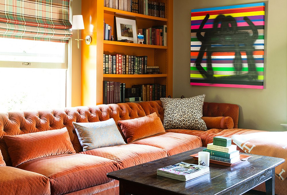 """Yager transformed this spare room, an """"empty box,"""" into a comfy den with built-in bookcases and a custom sectional upholstered in Schumacher's Paley Quilted Velvet."""