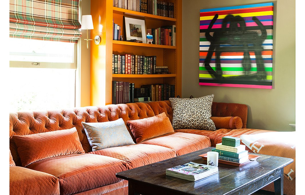 Because the rusty orange sofa is tonally compatible to the green walls, the effect is harmonious, even calm. Photo by Nicole LaMotte; design by Megan Rice Yager.
