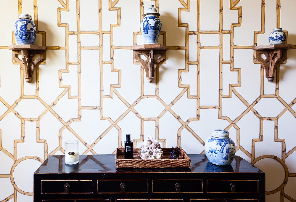 Baldwin Bamboo wallpaper from Scalamandré creates a graphic backdrop to ginger jars resting on Ballard Designs' brackets.
