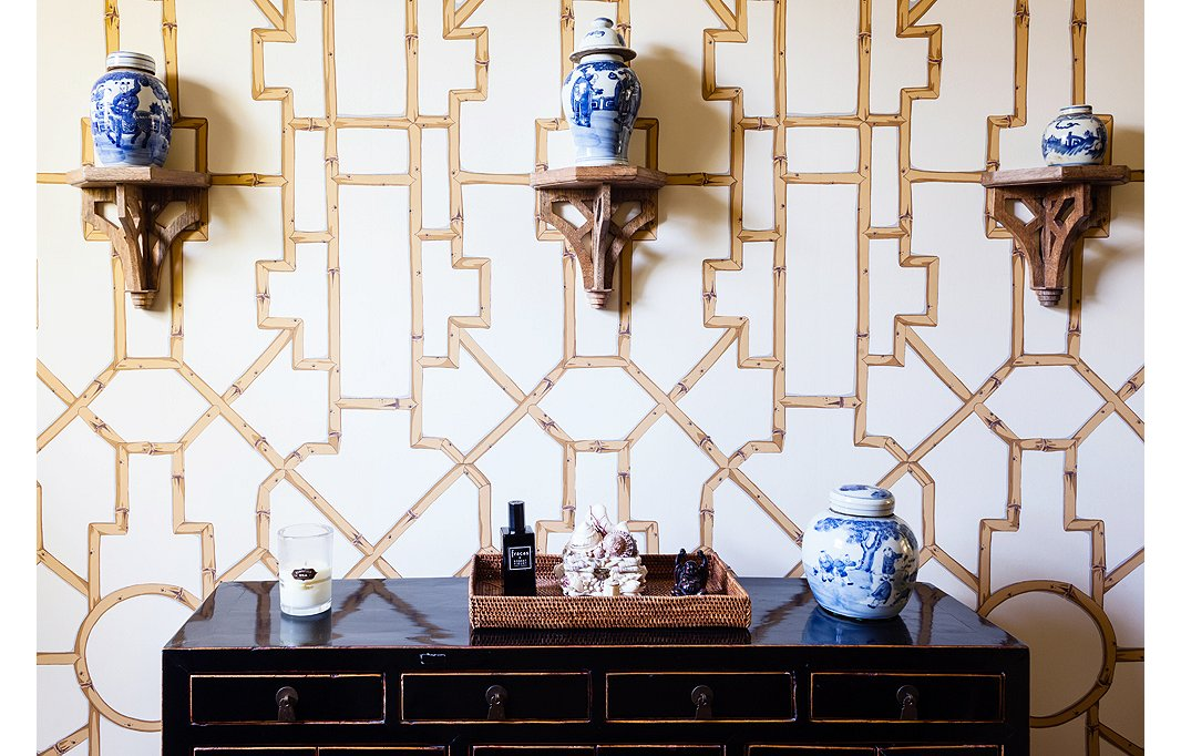 Baldwin Bamboo wallpaper from Scalamandré creates a graphic backdrop to ginger jars resting on brackets.