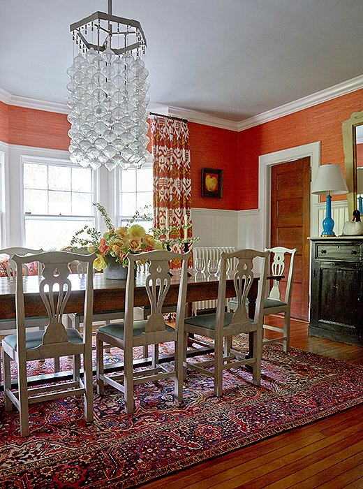 Mele covered two-thirds of the dining room walls with white wainscoting to temper the coral grasscloth that covers the reminder and painted the ceiling a subtle shade of blue.