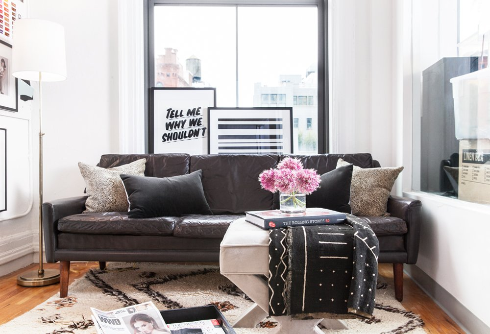 Atop a plush Moroccan rug, a midcentury leather sofa acts as a relaxed, no-pressure brainstorming zone where Reece can get creative away from her desk.