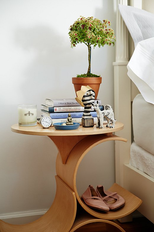 "Made by a favorite furniture maker in LA, Elana's bedside table is as long on function as it is on form. The curvy shape holds everything from slippers to a ton of magazines. Something organic is a must, as is an analog clock. ""The glow of the digital ones keeps me up at night."""