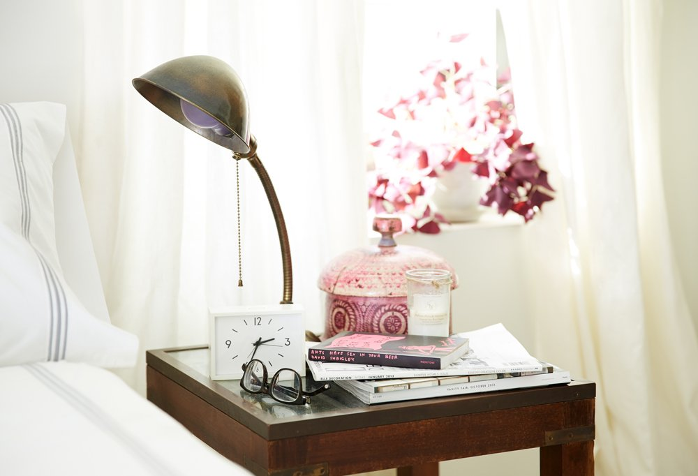 "Meghan's nightstand is just big enough to hold the essentials: a vintage spice box to corral daytime chaos, an antique lamp, and some reading material. Always nearby is a plant or some flowers. ""I like to look at nature when I wake up,"" says Meghan."