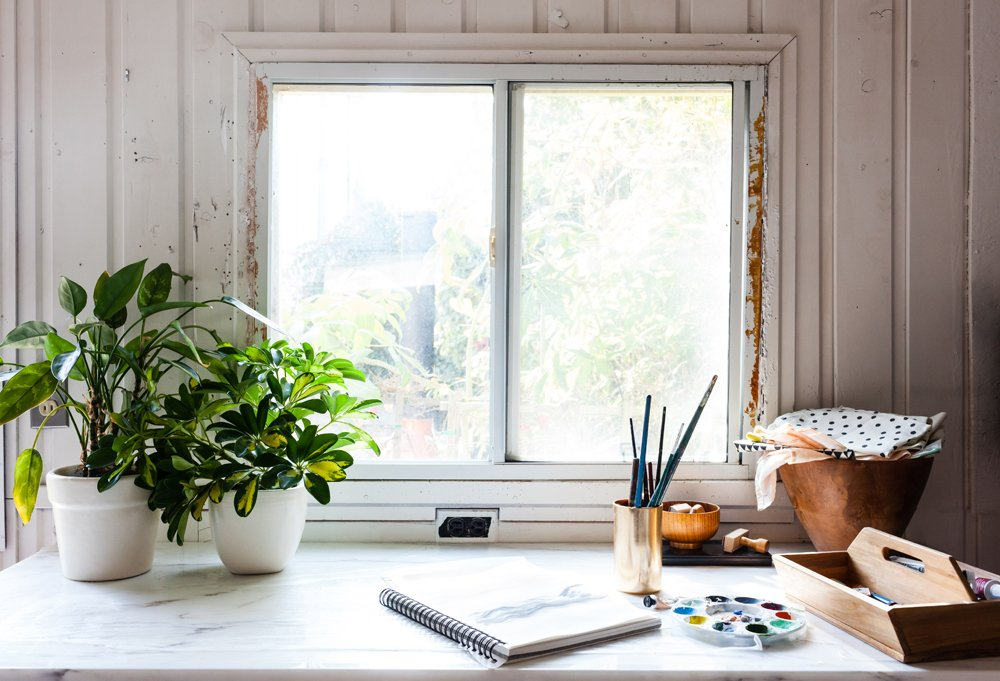 A standing worktable, like this one holding her paints and plants, is as essential in a studio to Sarah as oodles of natural light.