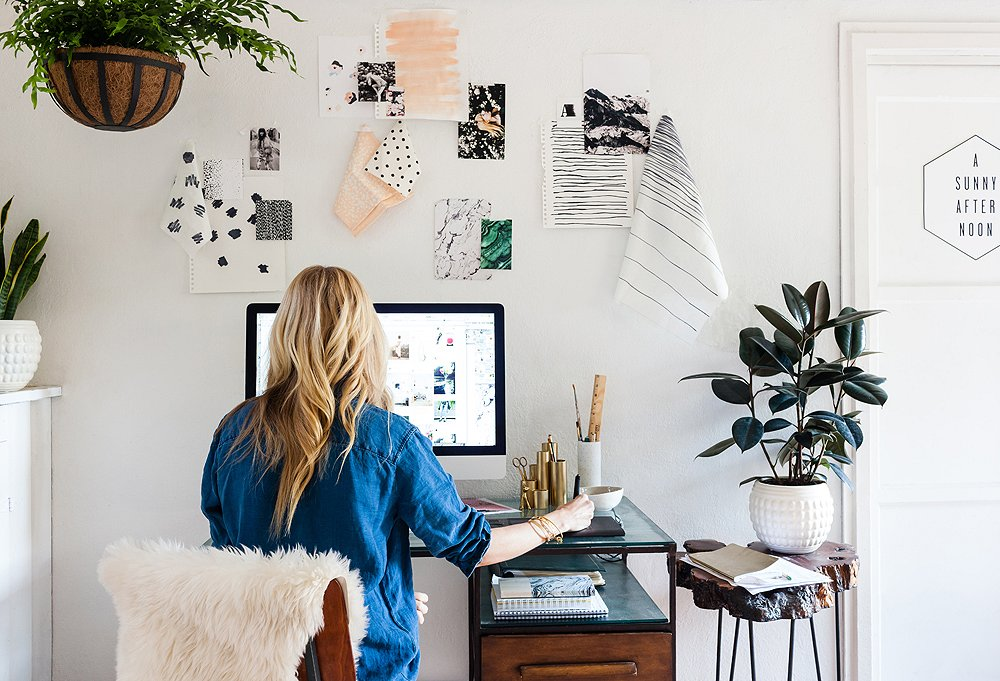 "Above Sarah's Anthropologie desk and flea-market, wood-slab side table hang bits and bobs from in-progress projects. No matter where she is in her studio, a plant or two is not far away. ""It's my way of bringing the outdoors in—they make me feel refreshed,"" she says."