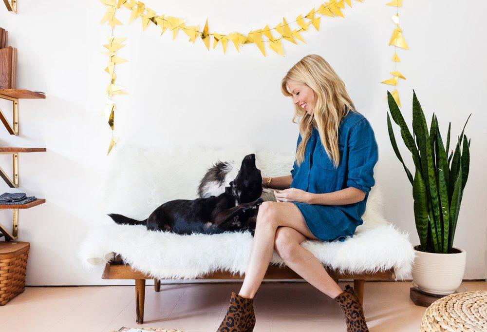 Under a gold garland she crafted for a past birthday, Sarah doles out belly rubs and ear scratches to her little buddies.