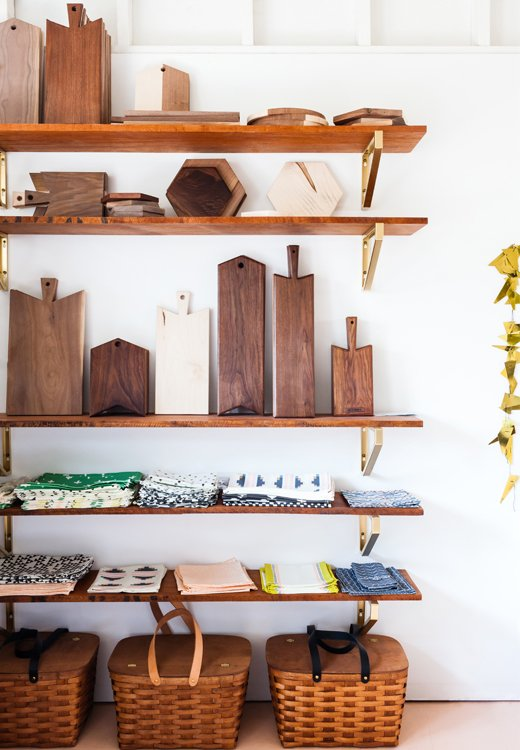 """So that her studio wouldn't feel left out from her house revamp, Sarah painted the tile floors Behr's Georgia Peach and installed African mahogany shelves with Ikea brackets. """"They were white, but I spray-painted them gold to make them look like brass,"""" she says."""