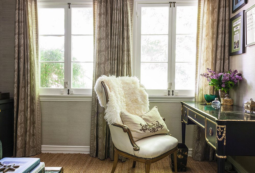 "Who says office furniture must be ""office furniture""? In Susan's space, a vintage chair tucks into a vintage desk under a wall hung with a handful of memorable press clippings about One Kings Lane. And the curtains? Made from one of her favorite Peter Dunham fabrics."