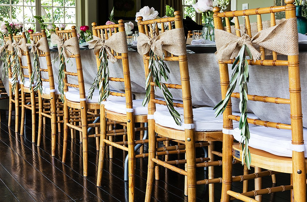Burlap ribbon tied in bows and embellished with olive branches upgraded the classic Chiavari rental chairs, adding a hit of femininity without sacrificing ease.