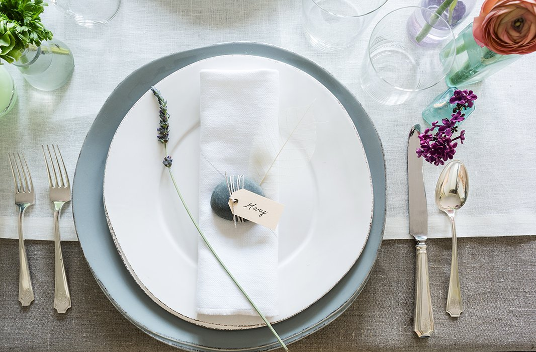 Place cards were tied to decorative river stones with twine. The imperfect shapes and serene hues of the oversize plates by Vietri added to the earthy look.