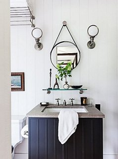 the small round mirror and vintage sconces add vintage charm to the guest bathroom of designer