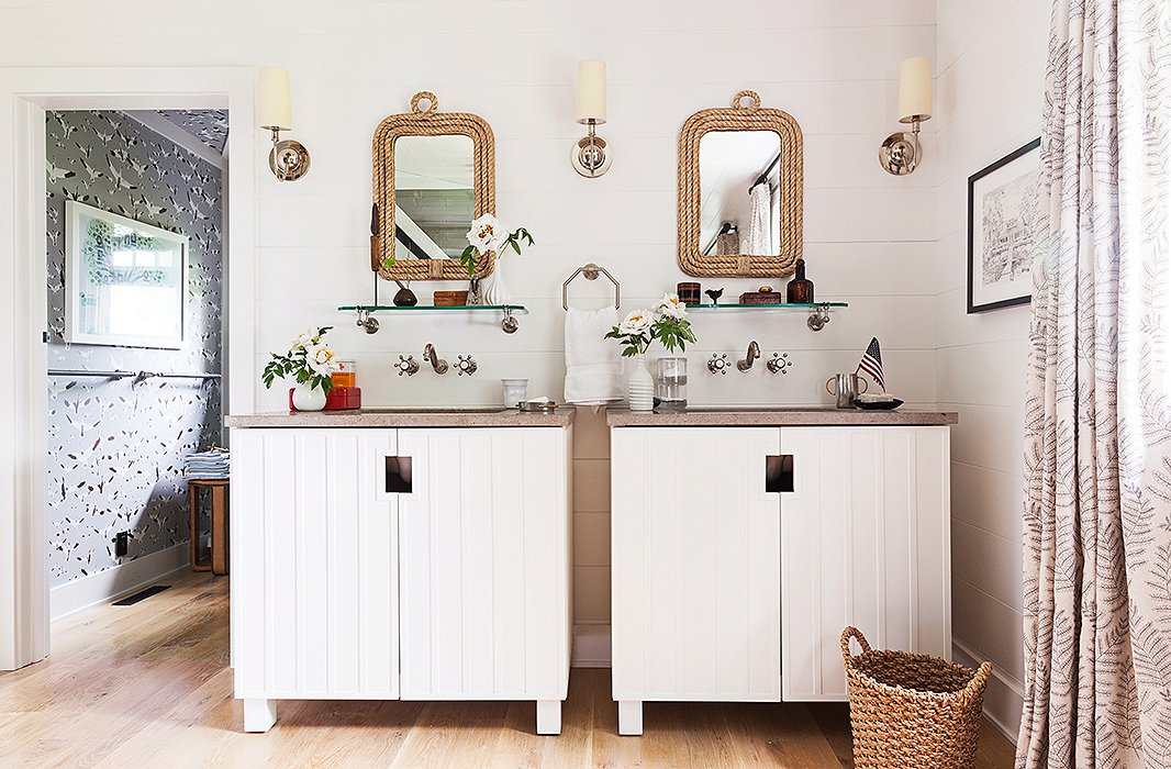 The master bath's rope-framed mirrors, wood paneling, vintage-inspired hardware, and bare wood floors are a perfect match for the lake house's old-fashioned, small-town setting.