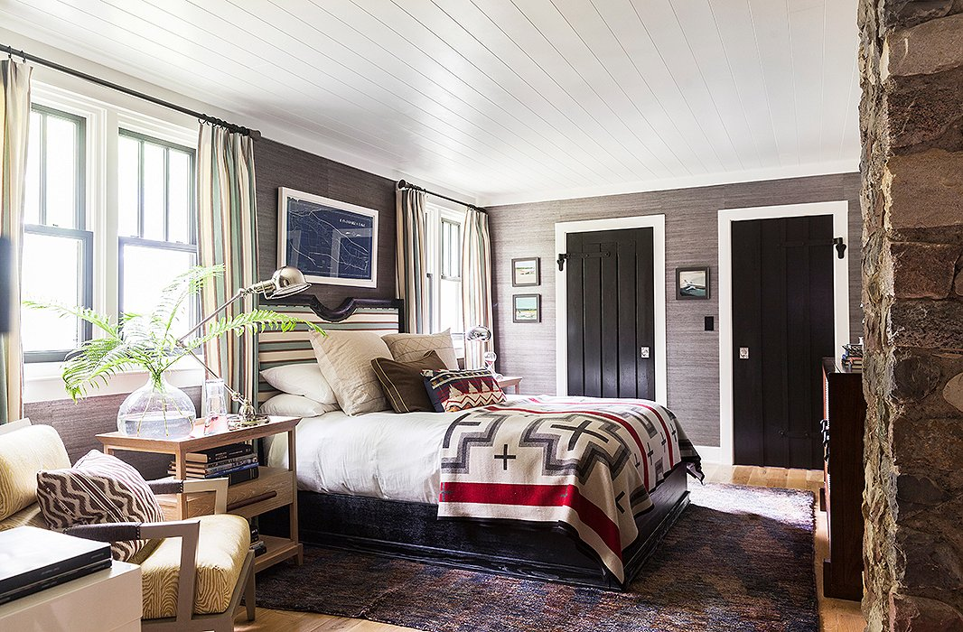 Fabric-covered walls, an upholstered headboard, and matching drapes make a sophisticated contrast to outdoorsy touches including a Pendleton blanket, a framed map, and dreamy seascapes.