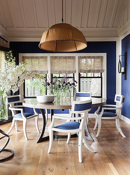 The walls of the dining room and the dining chairs are upholstered in the same rich blue and finished with the same nail-head trim. The muffling qualities of the fabric keeps dinner parties from getting too loud.