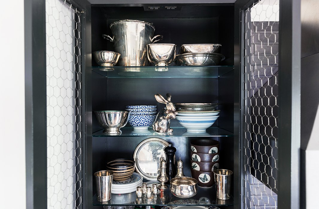 Chicken-wire cabinet fronts frame an unexpectedly elegant collection of gleaming serveware.