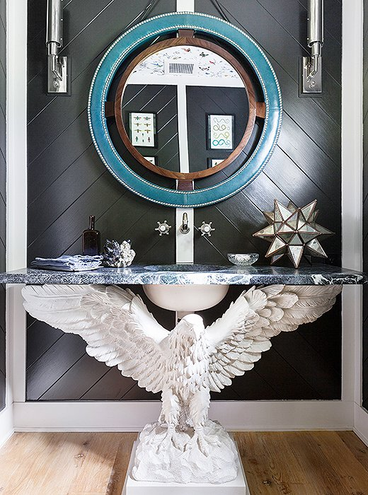Even without the massive eagle holding up the sink, the paneled black powder room would be striking; with it, the room is unforgettable.