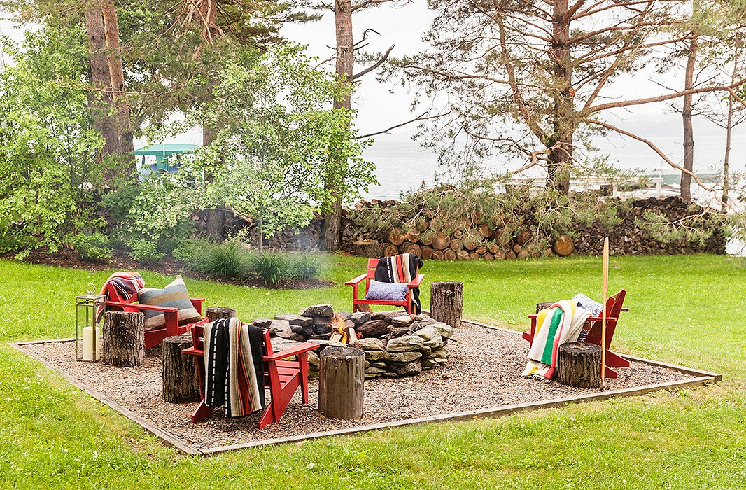 At the lakeside home of designer Thom Filicia, a stone fire pit anchors a grouping of cozied-up Adirondack chairs. Photo by Lesley Unruh.