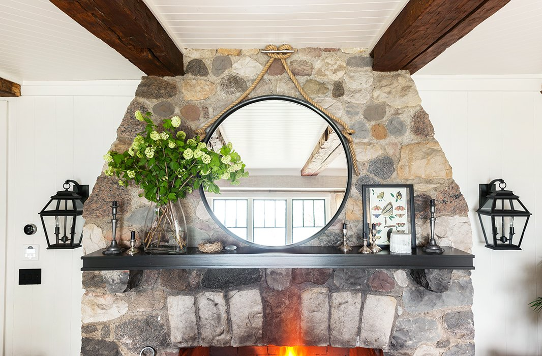 Nautical hardware and rope make the dramatically oversize modern mirror above the fireplace feel natural in a lakeside home.