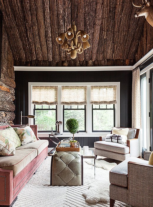 Rich fabrics—including sumptuous velvet, tufted leather, and plush sheepskin—feel even more luxurious against the backdrop of rough-hewn log walls.