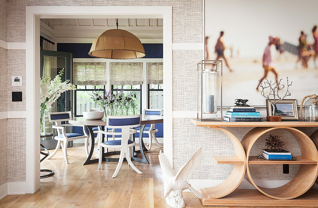 Repeating circular shapes—including the console, the dining table, the chandelier, and the metal end table—add a sense of dynamism and connect the living and dining rooms.