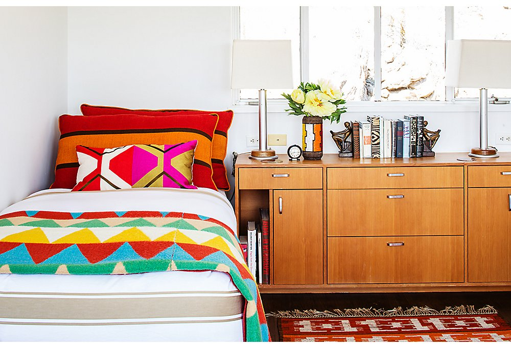 A guest room boasts a bevy of color and pattern, from vintage wool blankets to a pillow from Trina's home line. Vintage lighting, books, and pottery provide all the style and comforts of home.