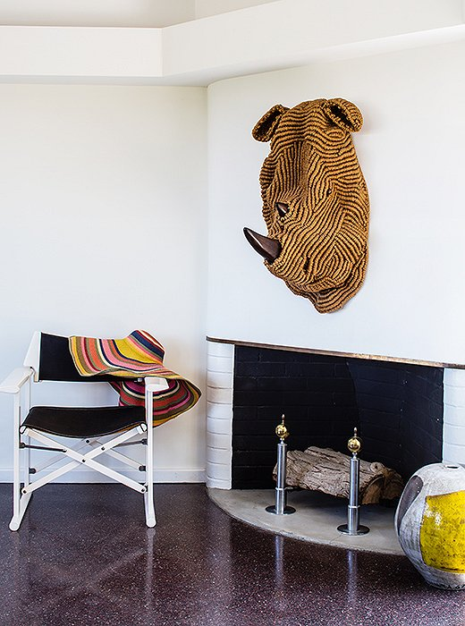 One of the couple's macramé animal heads takes center stage above the fireplace in the dining area.