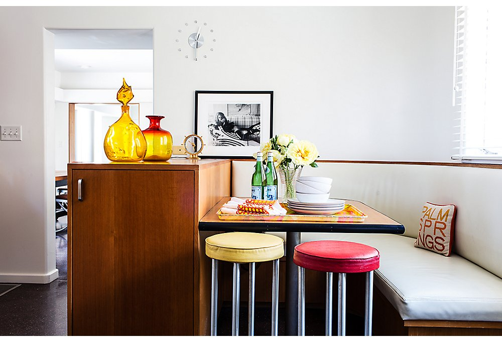 "The custom kitchen banquette was lovingly restored postfire after the couple saw the home's original floor plans. Jonathan bought the Steven Meisel photo at a charity auction. ""I loved the original editorial from Italian Vogue,"" says Trina."