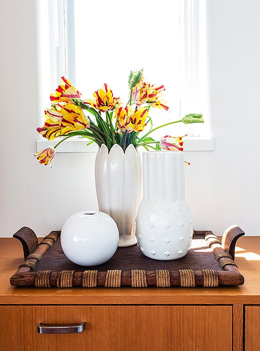 "A trio of vintage ceramic vases sits atop one of the home's numerous custom built-ins. ""It's so like a ship in that way,"" says Trina."