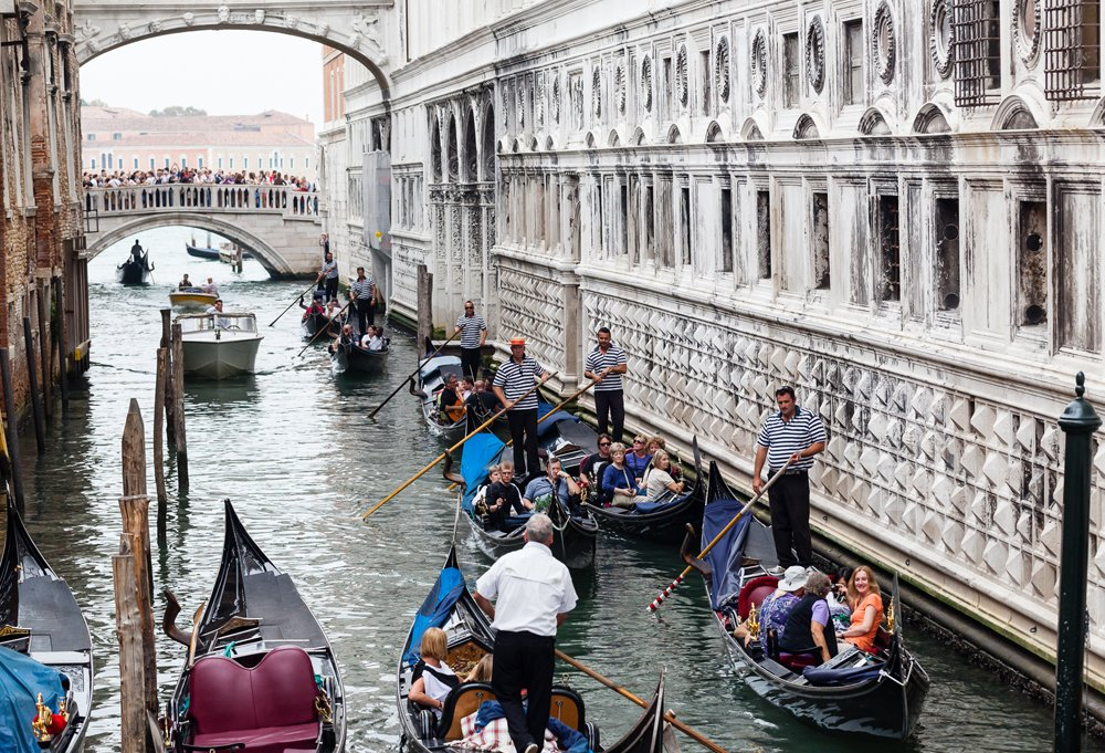 Gondolas on the go, crossing under the Bridge of Sighs. Fun fact: They're paddled, not poled, forward.