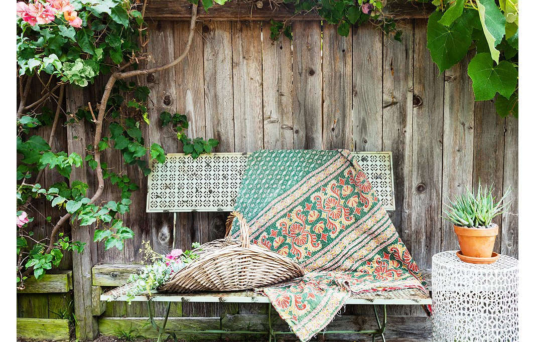 Morris creates a warm and welcoming sitting area by draping a colorful kantha throw over her One Kings Lane bench.