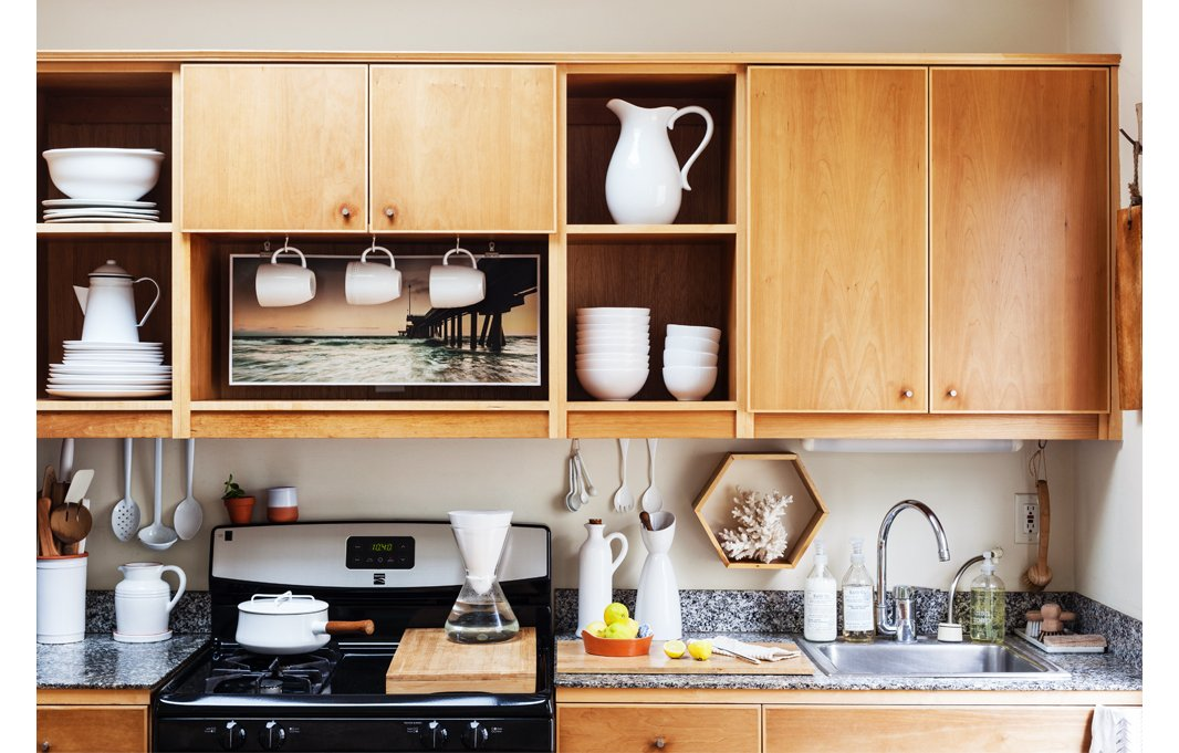 In her open kitchen, Morris opts for functional decor, putting her white dishware on display. Behind the cabinet doors? Drinking glasses fill out the open shelves nicely.