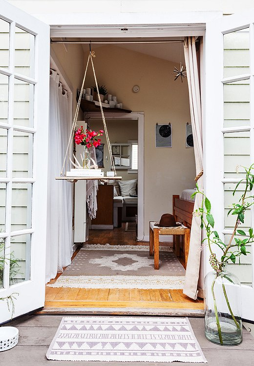 "The French doors in Morris's bedroom open up to a lovely garden space. ""We rarely close them,"" she says, ""but slide a sheer curtain across at night to keep the bugs at bay."""