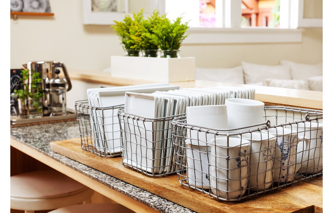 A smart idea for storage and entertaining: Morris keeps plates and mugs organized in metal baskets. No throw-away plates get used by this eco-friendly designer.