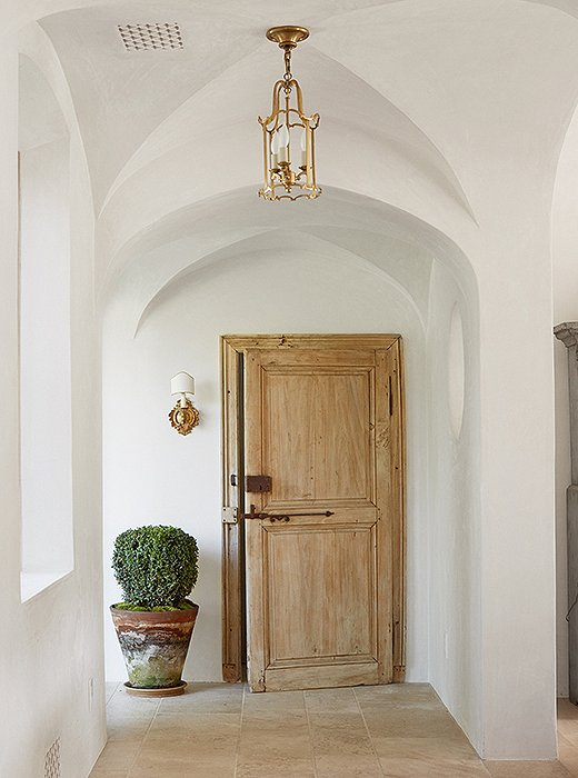 "The couple planted boxwoods and other trees and shrubs both outside and inside the home so that ""you feel like the lines blur between inside and out,"" says Steve. The small sconce beside the door is antique."