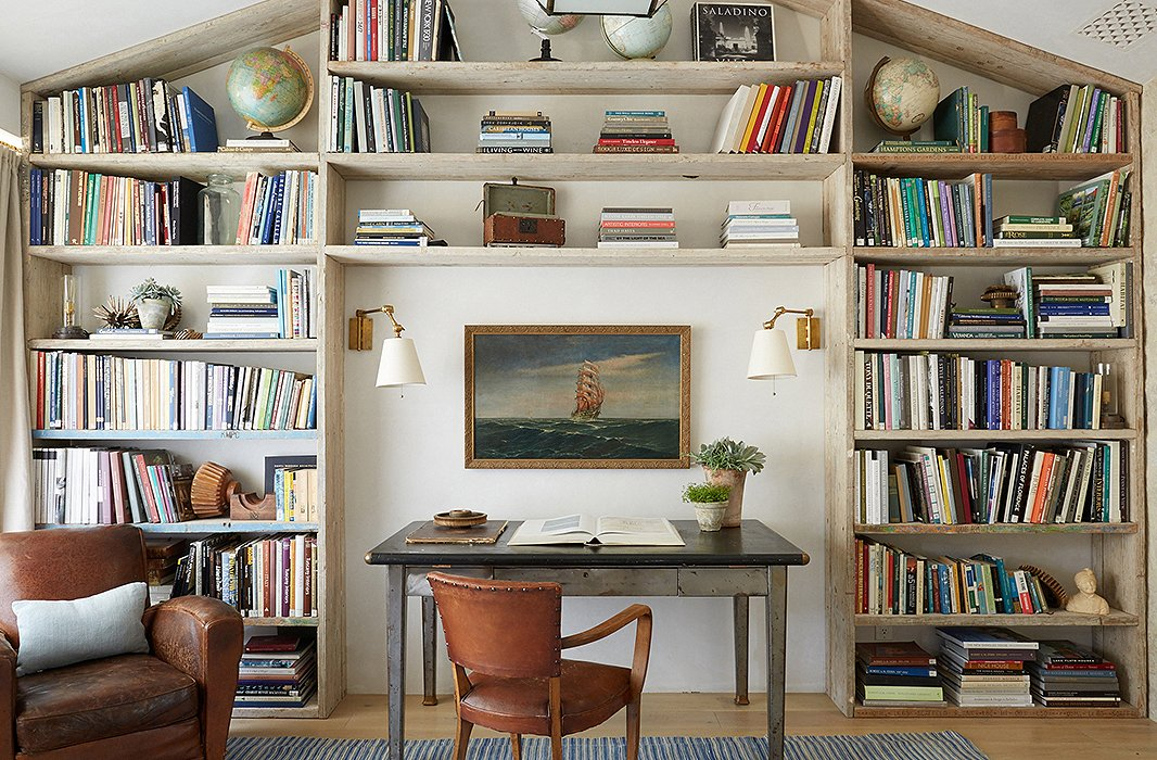 "In son Nick's bedroom, Steve designed a wall of shelving from repurposed scaffolding planks. ""He asked for a cool room with storage for his sneaker collection,"" says Brooke. ""We turned it into a library when he went to college."" The desk is a vintage industrial table."