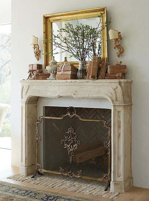 "Venetian sconces complement the master bedroom's French limestone mantel. ""I like using seasonal flowers to bring nature in, and I select objects that go with the palette of the room,"" says Brooke. ""The blush books echo the pink sunset we see each evening."" The fire screen belonged to Brooke's mother."