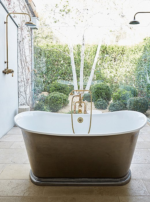 "To create a ""greenhouse atmosphere"" in the master bath, floor-to-ceiling sheets of glass envelop the pewter tub and shower and connect the space to the garden—filled with boxwoods, blue hydrangeas, and campanulas—just outside."