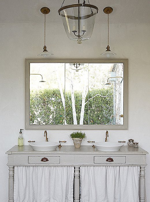 "A draper's table finds new life as a sink base and ""has the air of a potting table,"" Brooke says. The framed mirror has deep storage cabinets behind it. The bell-jar pendant was created from a vintage garden cloche."