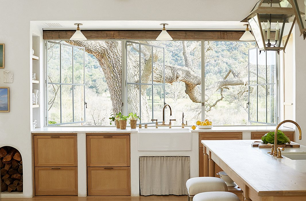"Wanting to harness ""every bit of natural light,"" Steve designed a wall of windows to connect inside and out and flood the room with sunshine. A farmhouse sink sits atop white-oak cabinets, a material used throughout the home for ""a sense of continuity."""