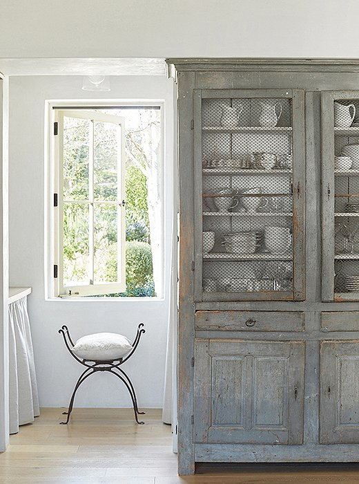 "The pair take frequent trips to Europe to source the antique furniture they love. In lieu of built-ins, Brooke uses an antique French cabinet for silverware and dishes. ""I tend to stick with white,"" she says."