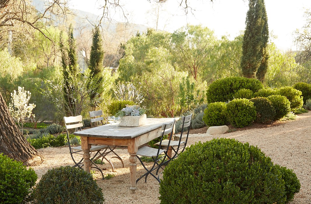 Peaceful and serene French Country courtyard with a farm table and bistro chairs. Patina Farm by Giannetti Home in Ojai, California, inspires with its natural approach to design with European inspired details. #patinafarm #courtyard #frenchcountry #gardens #gardeninspiration #farmhousestyle #farmhousedecor