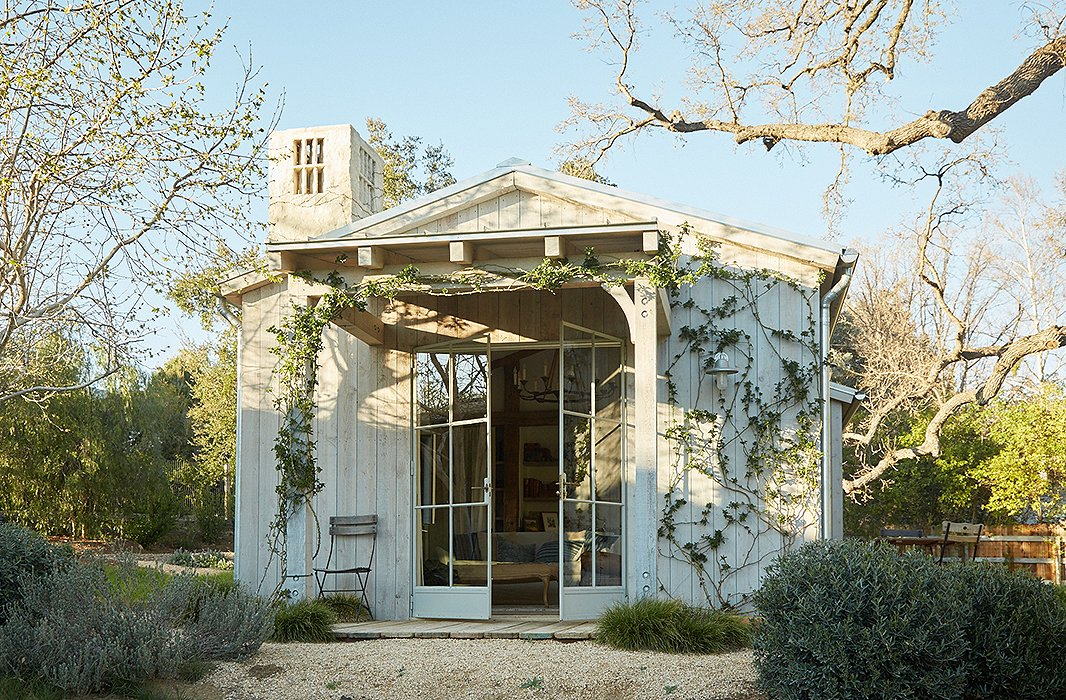 "The guesthouse is set next to an old oak tree. ""One of our dreams was that this would be a place for our family and friends to visit and share the world we created,"" says Brooke. Rose vines frame the entrance for an aromatic welcome."