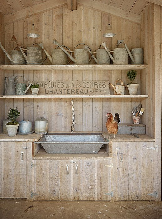 "A small kitchen in the coop has a galvanized sink made from a vintage trough. ""I store all of my kitchen and chicken supplies here,"" says Brooke. The vintage metal watering cans come from their frequent trips to flea markets and antiques shops."